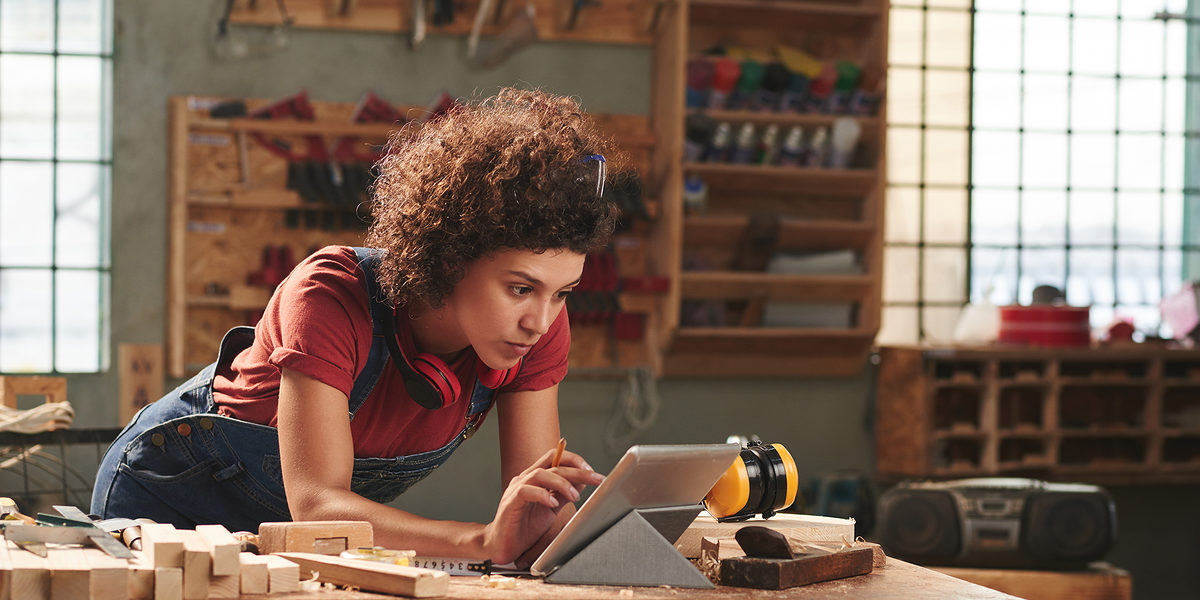 Young concentrated woman with curly hair reading instructions on digital tablet before working with wood Schlagwort(e): woman, female, young, attractive, curly, concentrated, digital, tablet, technology, internet, leaning, table, looking, reading, wifi, carpentry, joinery, timber, wood, wooden, plank, tool, skill, manual, equipment, professional, craft, craftsman, handyman, occupation, working, woodworking, workshop, woman, female, young, attractive, curly, concentrated, digital, tablet, technology, internet, leaning, table, looking, reading, wifi, carpentry, joinery, timber, wood, wooden, plank, tool, skill, manual, equipment, professional, craft, craftsman, handyman, occupation, working, woodworking, workshop